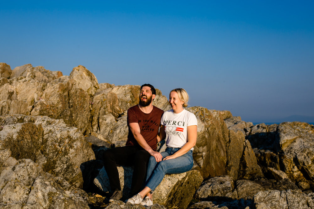 Laughing couple on a fun and relaxed pre wedding shoot in Anglesey.