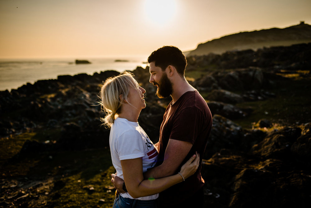 Anglesey pre wedding shoot. A couple facing each other as the sun sets.
