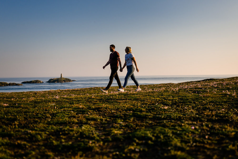 Walking couple on the headland over looking the sea in Anglesey, Wales.