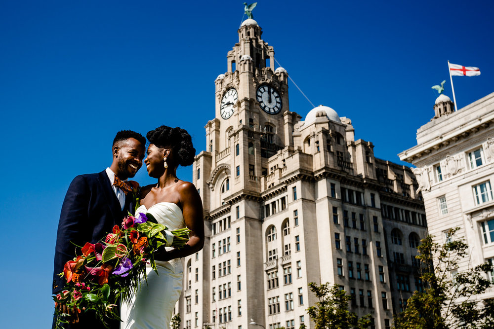 Bride & Groom with a colourful, tropical bouquet standing and smiling at each other in front of the Liver Building, by Liverpool wedding photographers.