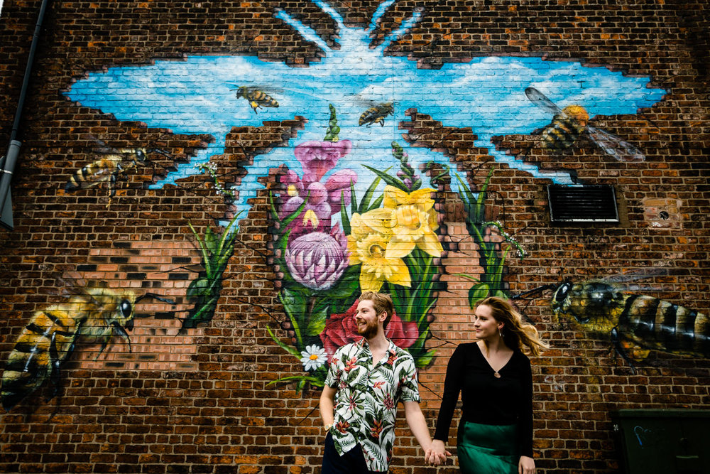 Colourful pre wedding shoot, a couple holding hands in front of a Manchester Bee ahead of their wedding day in Chorlton.