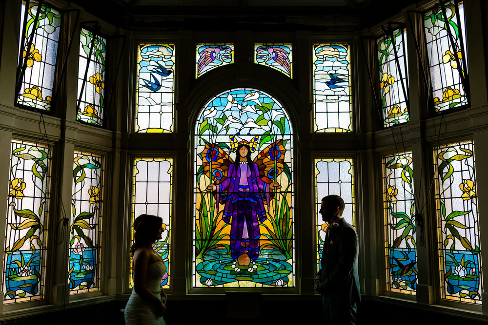 Bride & Groom in front of the stunning stained glass windows of the Turkish Baths at Victoria Baths wedding photography