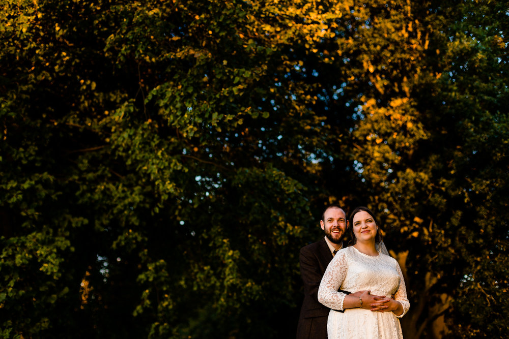 A bride and groom cuddle watching the sunset on a colourful autumn day at their Chester wedding at Trafford Hall.