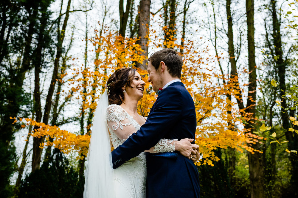 Bride and groom with a colourful autumn backdrop in the forest grounds of Tyn Dwr Hall, by wedding photographers Zoe & Tom
