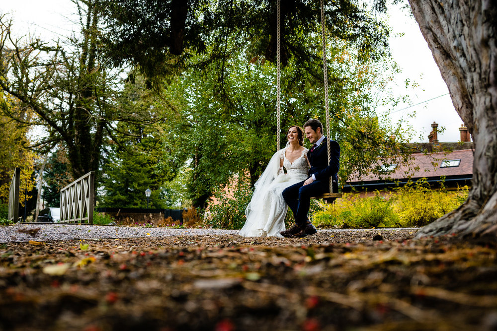 Nicola and Dave sat on the swing at Tyn Dwr Hall on their wedding day