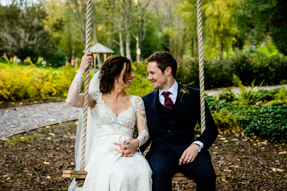 Bride and Groom sat on a swing in woodland in Wales