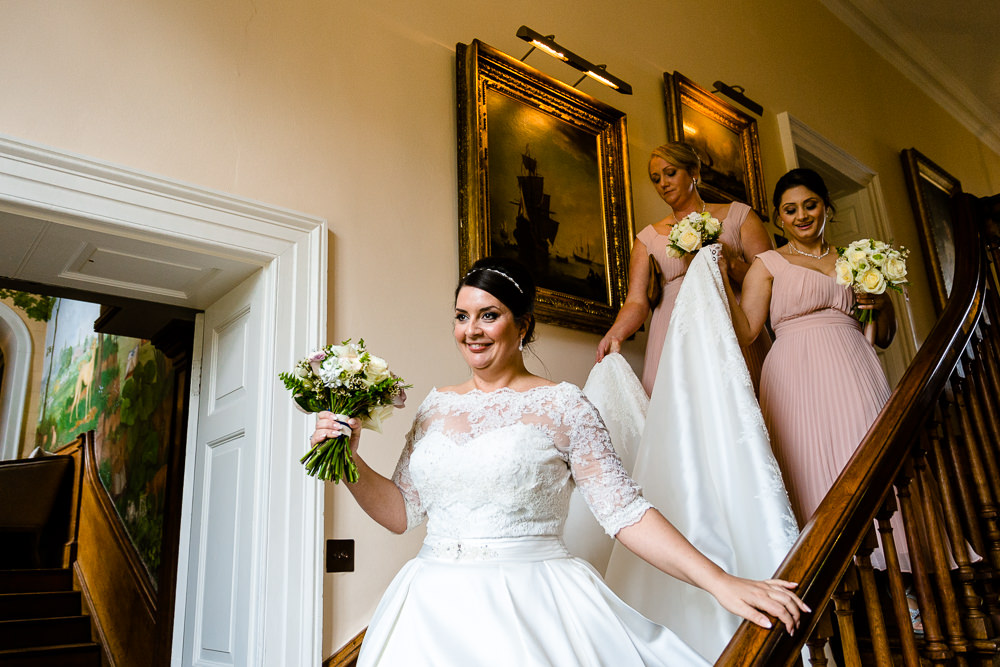 A bride on the stairs at Iscoyd Park ahead of her wedding ceremony