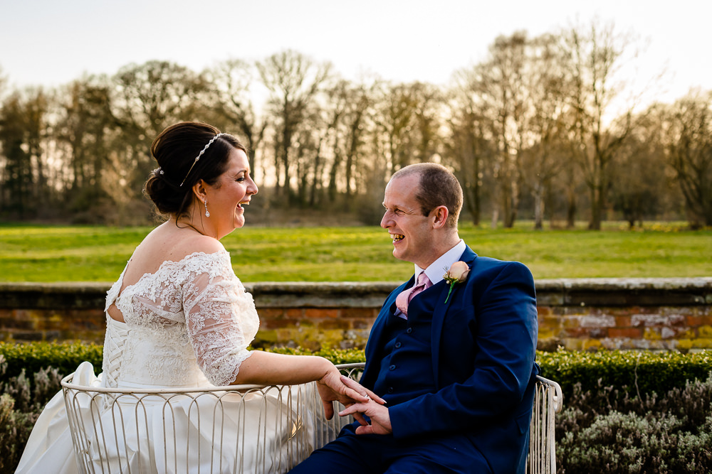 Kate and Paul sit and laugh together at sunset in the gardens at Iscoyd Park on their wedding day by wedding photographer About Today Photography.