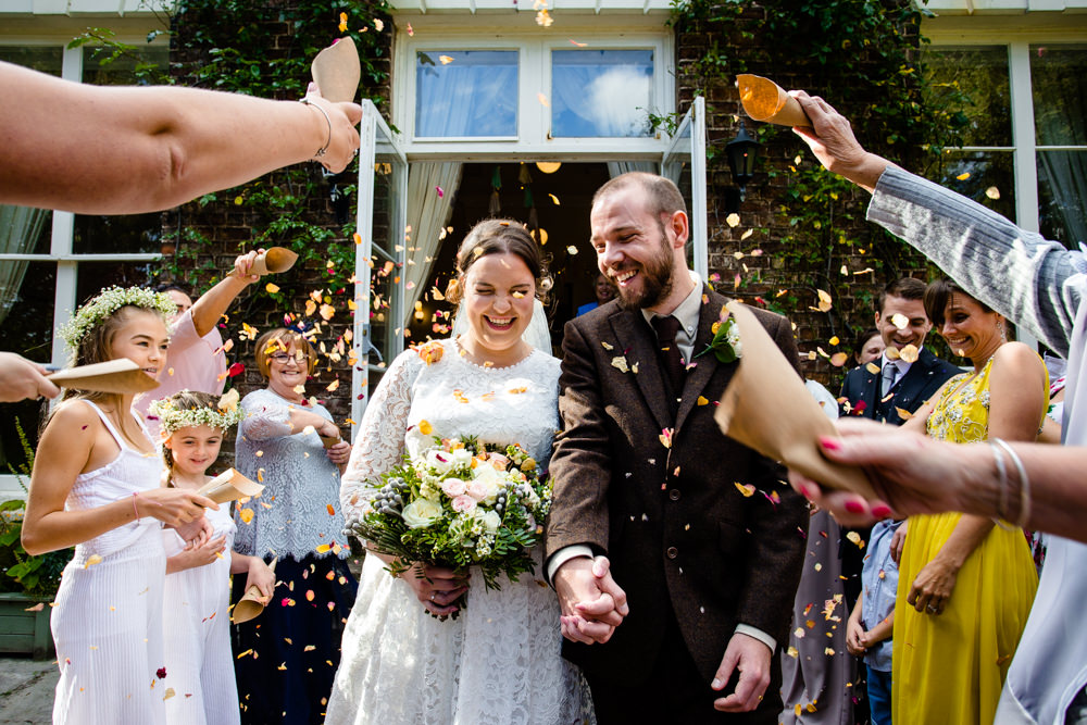 Guest throw confetti at a newly married couple at their outdoot garden ceremony at Trafford Hall Chester.