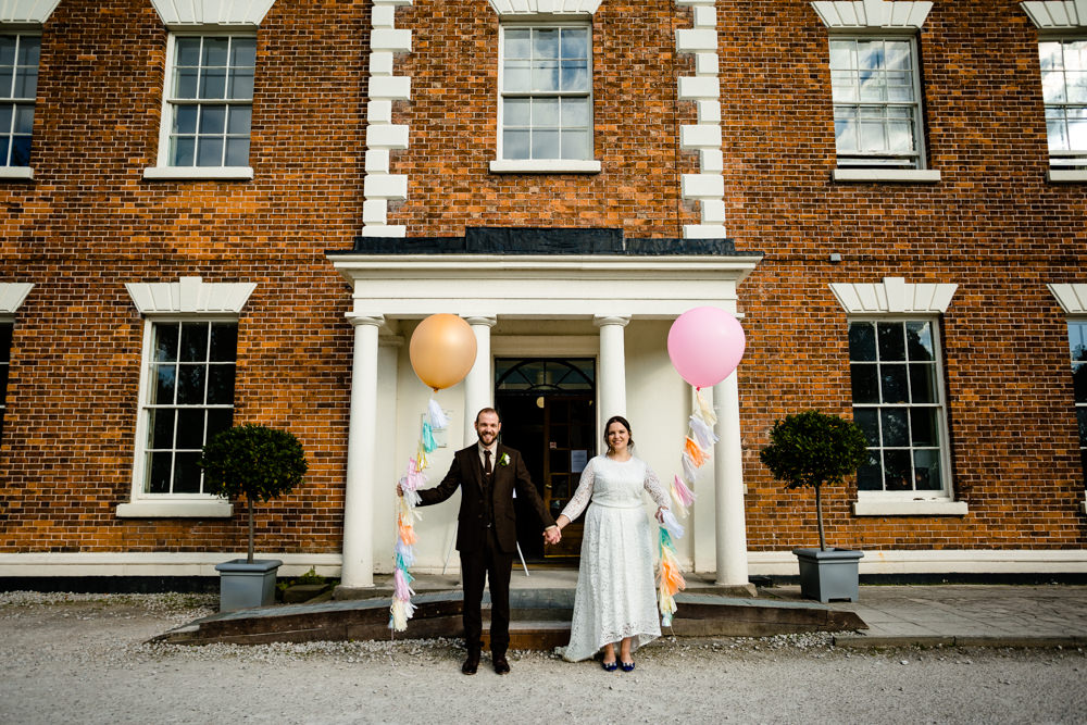 A bride and groom holding giant balloons with colourful tassels, at their Chester wedding outside a hall.