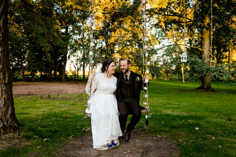 A couple sat on a swing in a forest in dappled sunlight on their Chester wedding day.