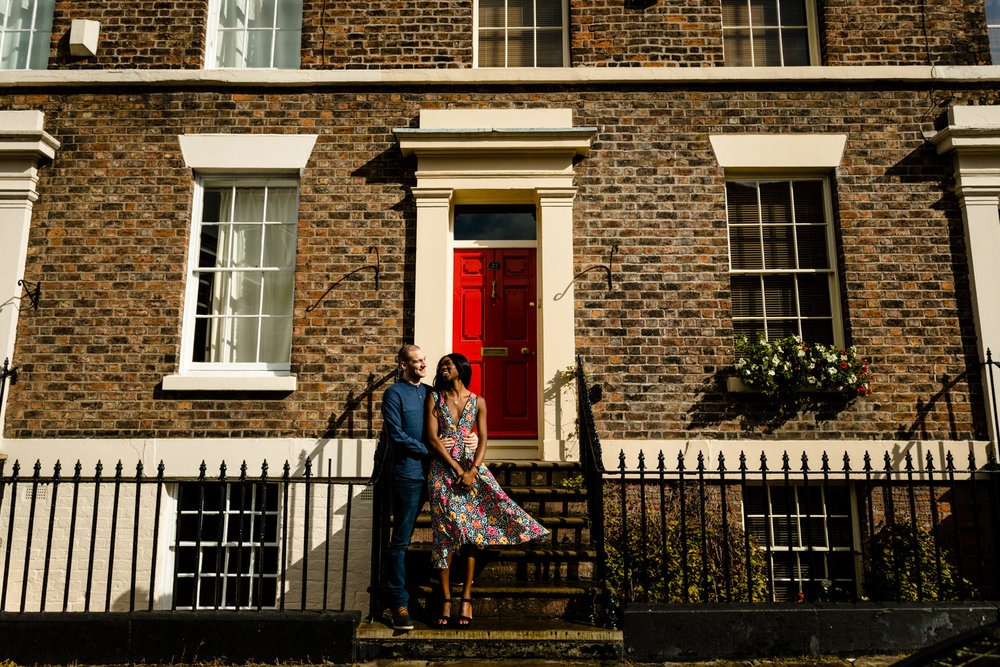 Creative wedding photographers Liverpool, an engaged couple stood on Georgian steps in front of a colourful red door