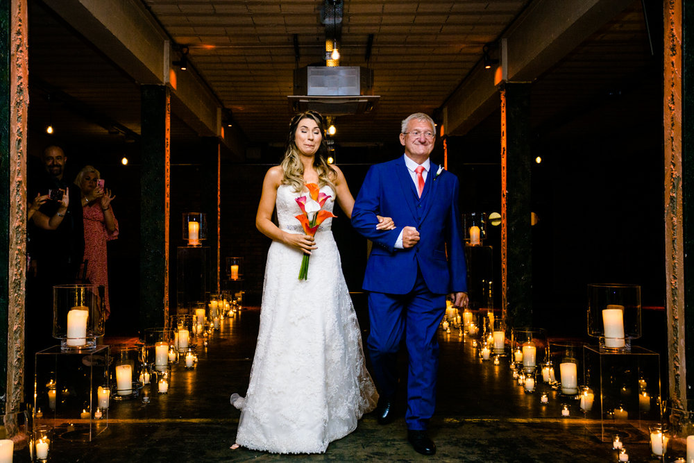 An emotional bride walking down the aisle at Victoria Warehousewedding photography