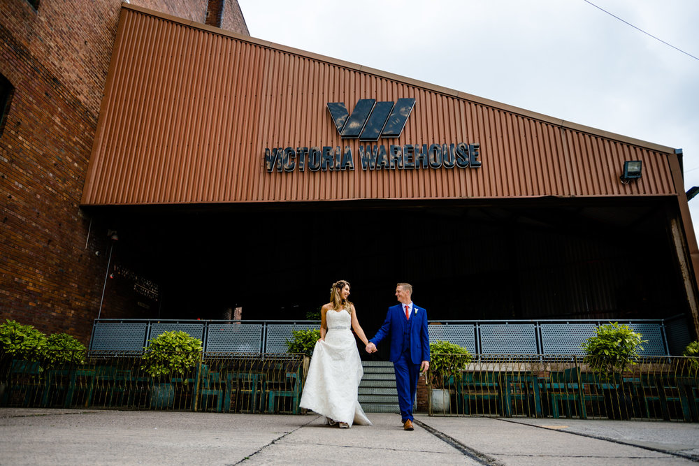 A couple walking together by wedding photographers Victoria Warehouse