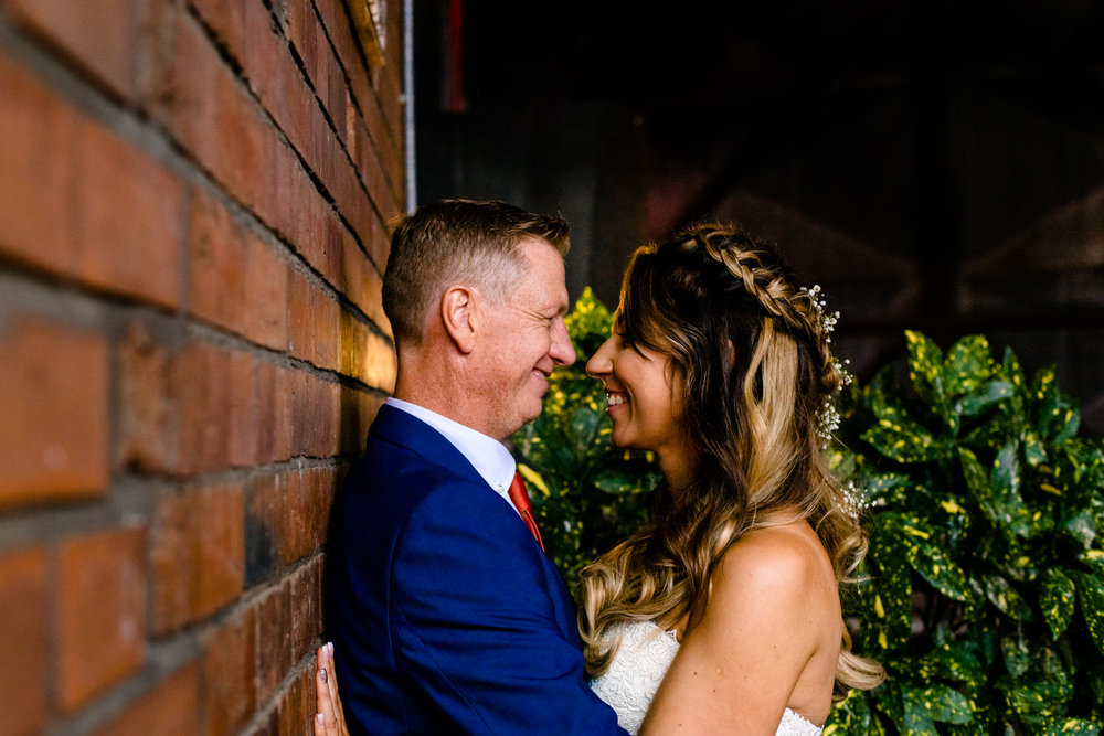 A wedding photo at Victoria Warehouse, a bride and groom facing each other.