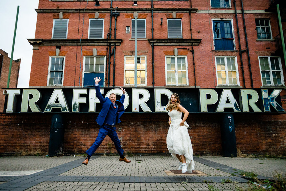 A couple jumping in the air, weddingphotographs Victoria Warehouse