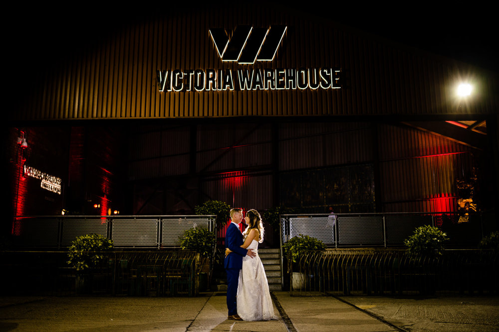 A bride and groom stood outside Victoria Warehouse at night in Manchester.
