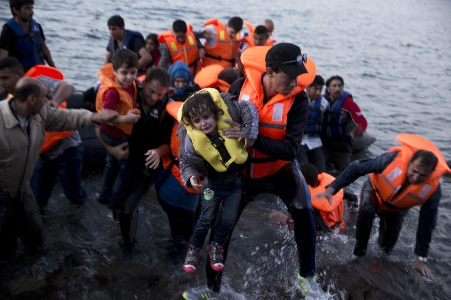 """Syrian refugees arrive aboard a dinghy after crossing from Turkey to the island of Lesbos, Greece. A boat with 46 migrants has sunk Sunday in Greece, and the coast guard says it is searching for 26 missing off the eastern Aegean island of Lesbos. Seeing their community's story in the plight of those boarding tiny, rickety boats for Europe, some Vietnamese-Americans are reaching out to help. In addition to the 4-mile walk, some in California have started a Twitter campaign to generate compassion for those taking to the seas and a fundraising drive to support migrant rescue efforts. The U.S. has announced plans to receive 10,000 Syrian refugees in the next year. (AP Photo/Petros Giannakouris, File)"""