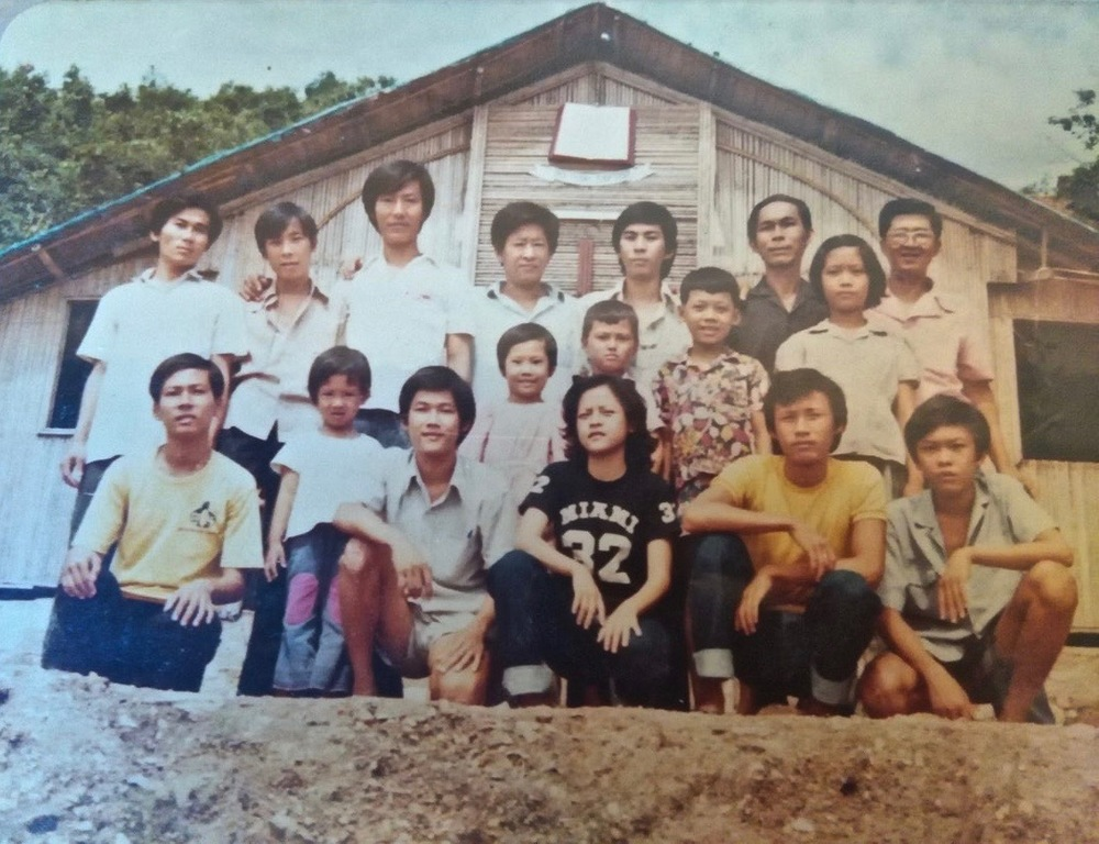 A group photo in front of the Baptist Church in the Lam Sing Camp, the first camp we went to after making it to Thailand. My father is in the back row, second from the right, standing next to the captain of our boat. My brother and I are standing in front of them, the two on the far right.