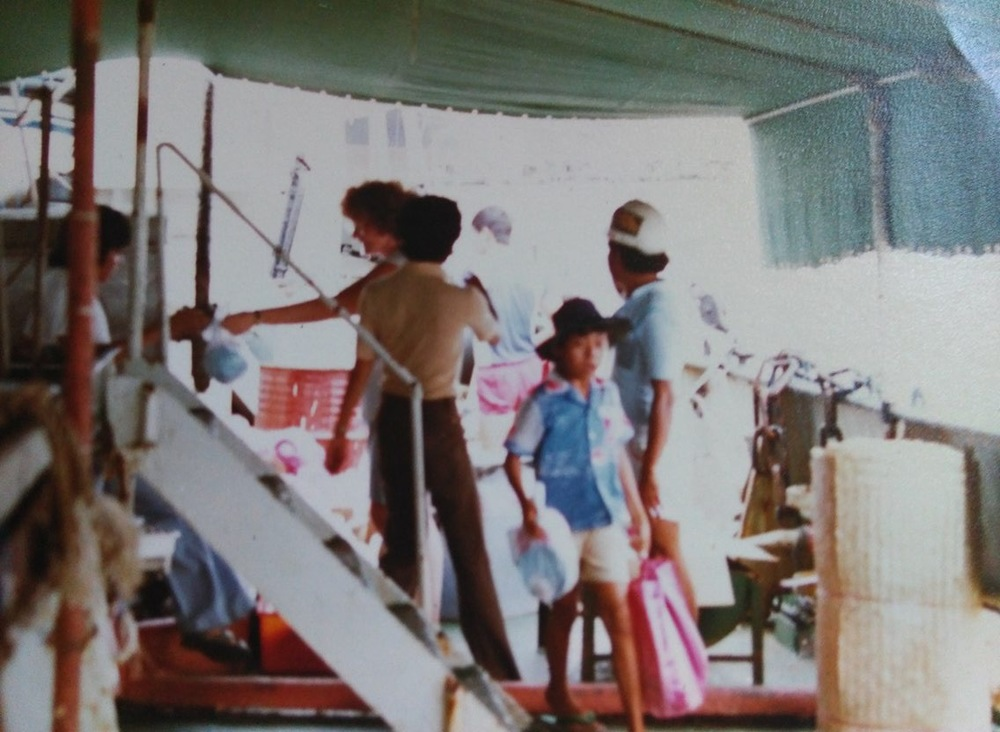 This picture was taken on boat that took us from the second camp I was in to Galang Camp in Indonesia. My brother Tom is the little boy in the middle of the photo.