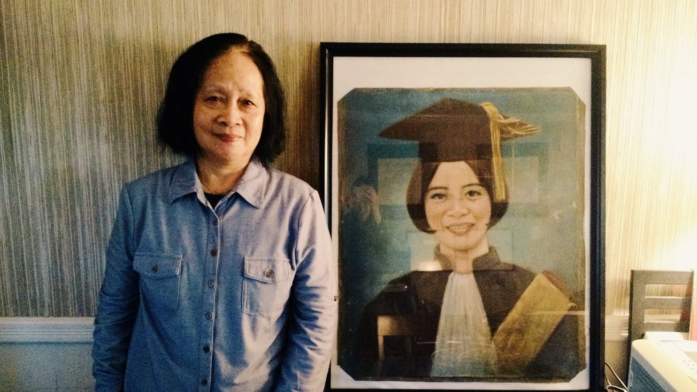 Thien Tho Ngoc Nguyen standing next to a painted portrait of herself to celebrate her graduation from Dalat University.