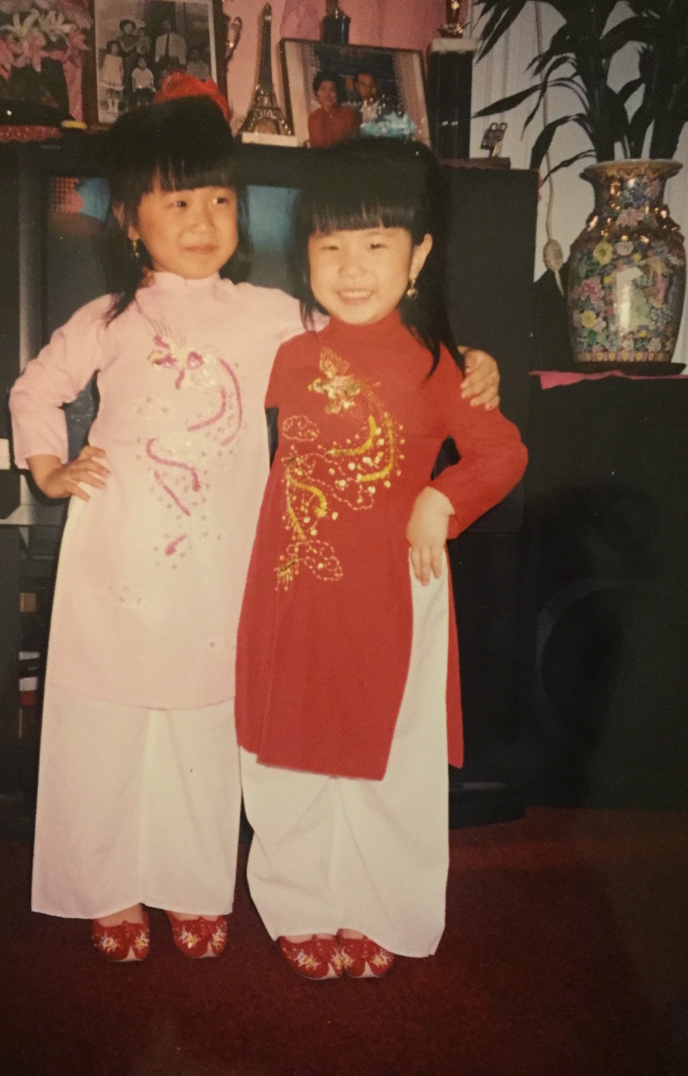 My sister and I are both wearing an áo dài, traditional Vietnamese attire.