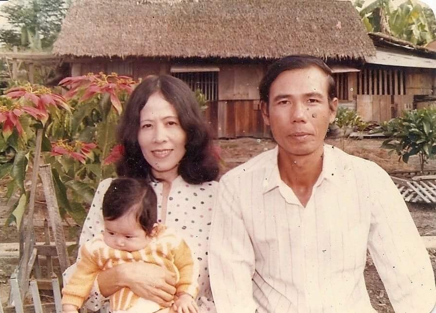 Nguyen Huu Thao, his wife, and one of his daughters in front of their house back in Vietnam.