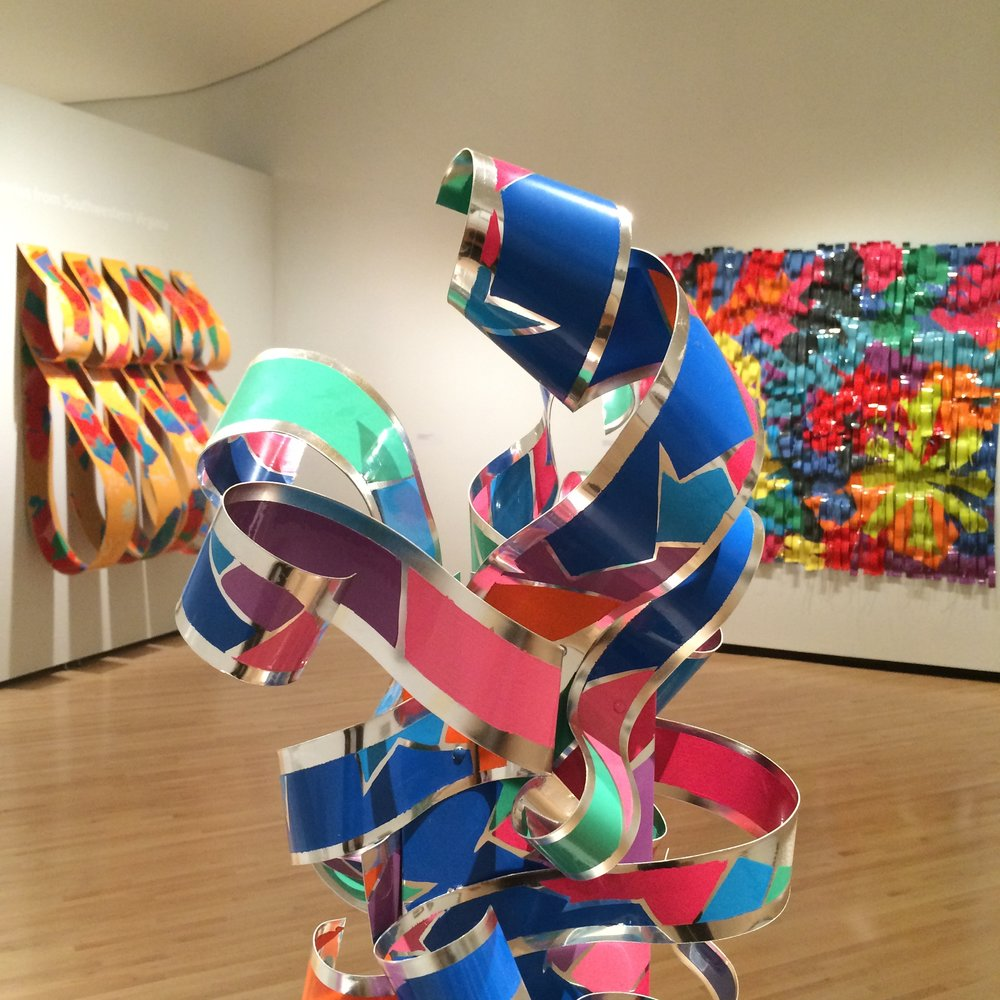Enamel on aluminum works by Roanoke artist Dorothy Gillespie in  Legacies: Honoring Artistic Luminaries from Southwestern Virginia  at the Taubman Museum of Art. Foreground:  Ribboned Presence , 1993. Rear left:  Tiered Arrangement III . Rear right:  Colorfall Series, Garden , 1993.
