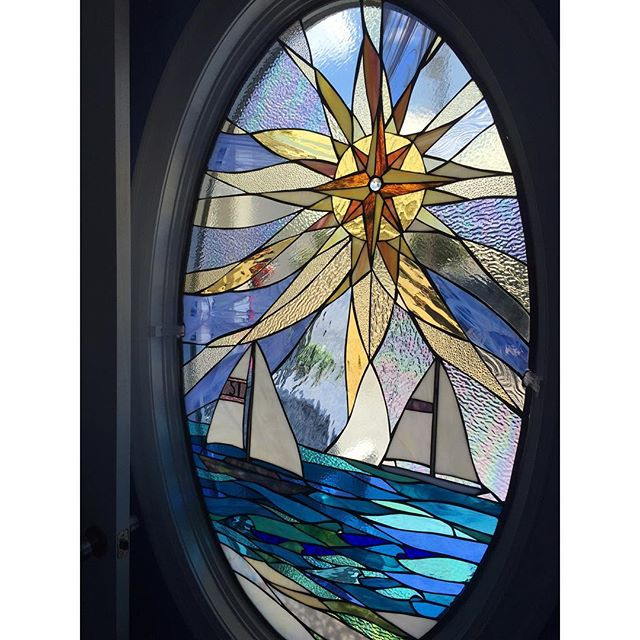 Custom oval compass rose sun complete and installed in door frame.