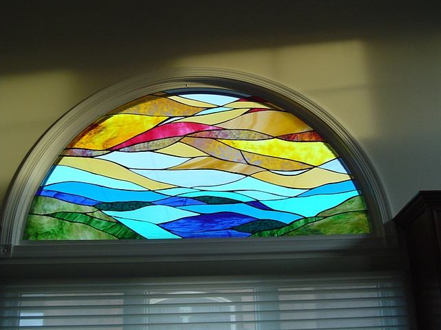 """Earth, Ocean, Sky"" kitchen  Stained Glass  Two similar panels were created for this residence (one for the kitchen and one for the bathroom). The home owner wanted continuity from room to room for the exterior views of his house. When the house is lit at night, his neighbors get a visual treat.  Designing and fabrication typically are all done in our studio located on Long Beach Island, NJ. Custom work is one of our specialties, evidenced by our many happy repeat clients. We have a team of carpenters working with us for all your installation needs as well."