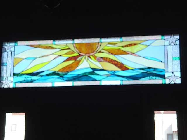 Sunrise Over Brigantine (installed)  Stained Glass  This is a view of the transom window after installation. The rich turquoise and warm golden yellows provide an inviting accent to the entryway of this private residence.  This piece is now held in the Schimek Collection.  Designing and fabrication typically are all done in our studio located on Long Beach Island, NJ. Custom work is one of our specialties, evidenced by our many happy repeat clients. We have a team of carpenters working with us for all your installation needs as well.
