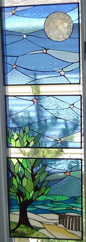 """Beach Entrance, Full Moon""  Stained glass  My clients wanted to depict the beach entrance at the end of their street. At the time of the commission, I had an incredible photo by Ann Coen hanging in my gallery featuring surfers in the water with a giant full moon. This inspired my clients and they wanted me to include the full moon in the design. This worked out well because they also wanted deep and rich blues. Incidentally, this was my first commission after I moved into my new studio space in Haven Beach.  Held in private collection in Haven Beach.  Designing and fabrication typically are all done in our studio located on Long Beach Island, NJ. Custom work is one of our specialties, evidenced by our many happy repeat clients. We have a team of carpenters working with us for all your installation needs as well."
