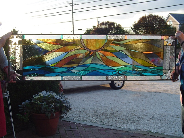 Sunrise Over Brigantine  Stained Glass  This is a view of the transom window prior to installation. The rich turquoise and warm golden yellows provide an inviting accent to the entryway of this private residence.  This piece is now held in the Schimek Collection.  Designing and fabrication typically are all done in our studio located on Long Beach Island, NJ. Custom work is one of our specialties, evidenced by our many happy repeat clients. We have a team of carpenters working with us for all your installation needs as well.