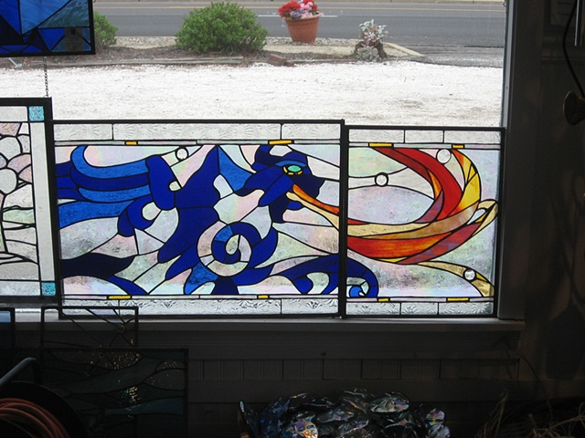 """The Dragon"" partial view pre-intallation  Stained Glass  This is a partial, pre-installation view of ""The Dragon"". The design for the three panels in this series was inspired by the tiles in the home owner's powder room. They are installed in a historic home in Beach Haven, NJ.  Designing and fabrication typically are all done in our studio located on Long Beach Island, NJ. Custom work is one of our specialties, evidenced by our many happy repeat clients. We have a team of carpenters working with us for all your installation needs as well."