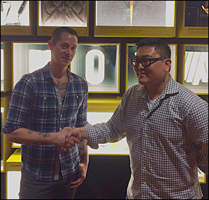 Starbucks' Josh Barrows (left) and Amazon.com's Ben Grace share a hand-shake at MOHAI after being elected to the South Lake Union Community Council.