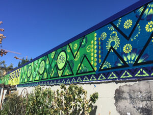 "The completed 100-foot-long ""A Dream for Cascade"" mural at the entrain to the Y at Cascade People's Center (Photo: Josh Epstein)"