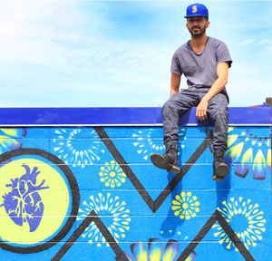 "Artist Adream de Valdivia sits atop the Y at Cascade Peoples Center and his civic mural ""A dream for Cascade"" completed in late July. (Photo: Josh Epstein)"