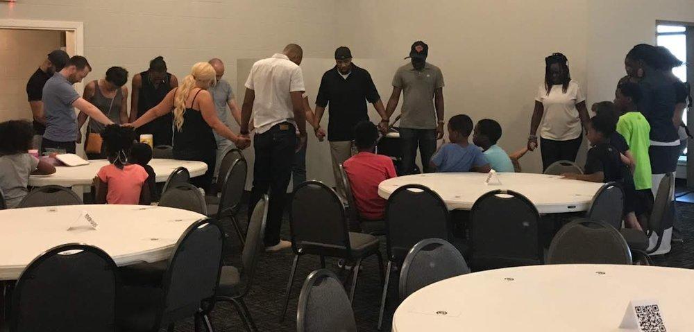 Kaynenn leading the set-up team in prayer before the info/prayer meeting.