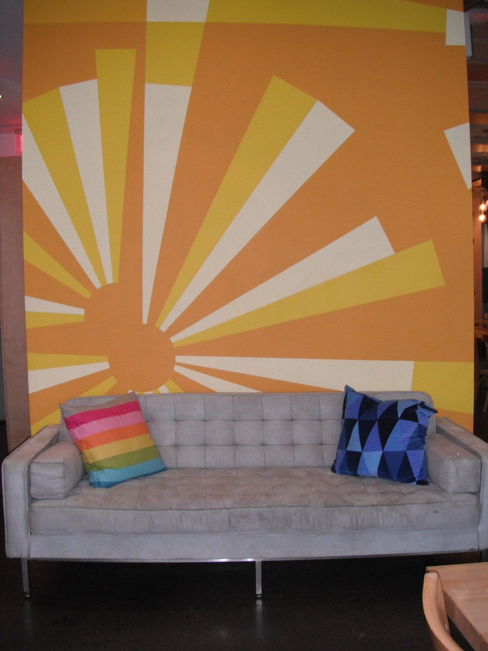 Picture of colourful wall and grey couch.