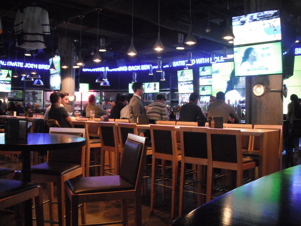 Picture of interior of restaurant. Many TV screens and tables.