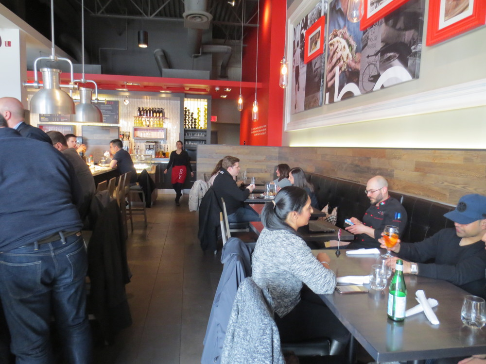 Picture of interior of restaurant. Pathway with people sitting at standard height tables.