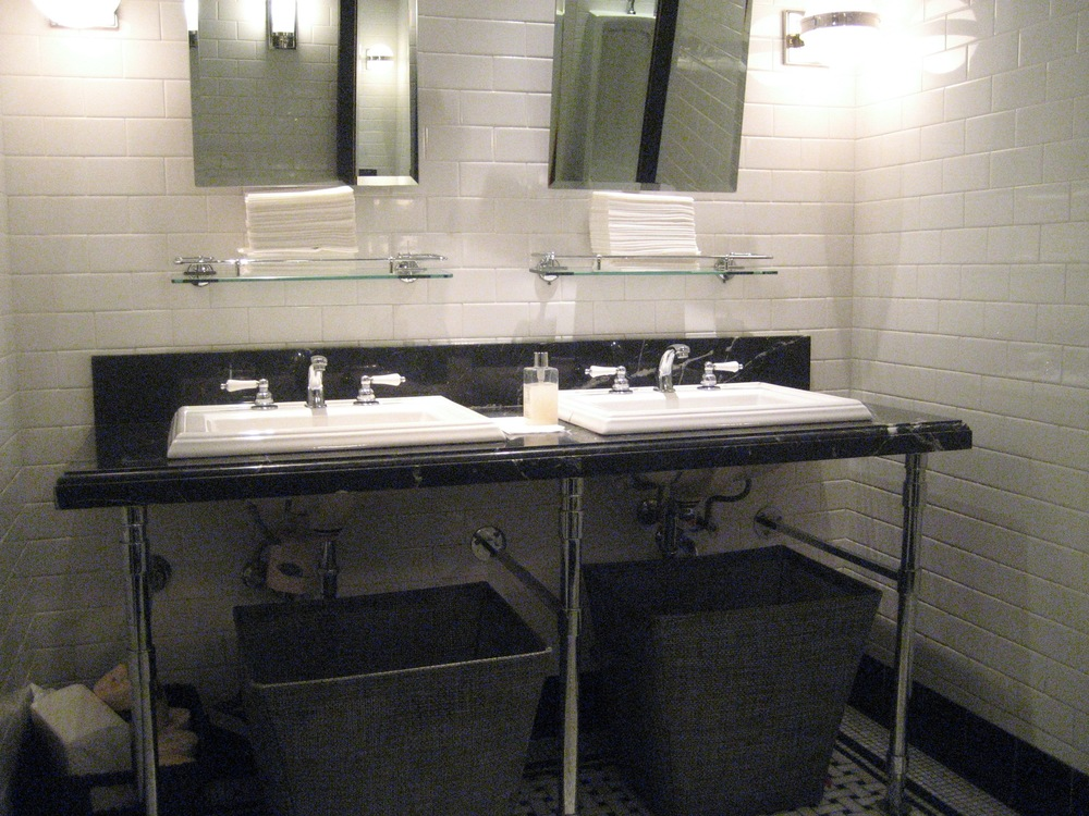 Picture of sinks in the washroom with waste basket obstructing space