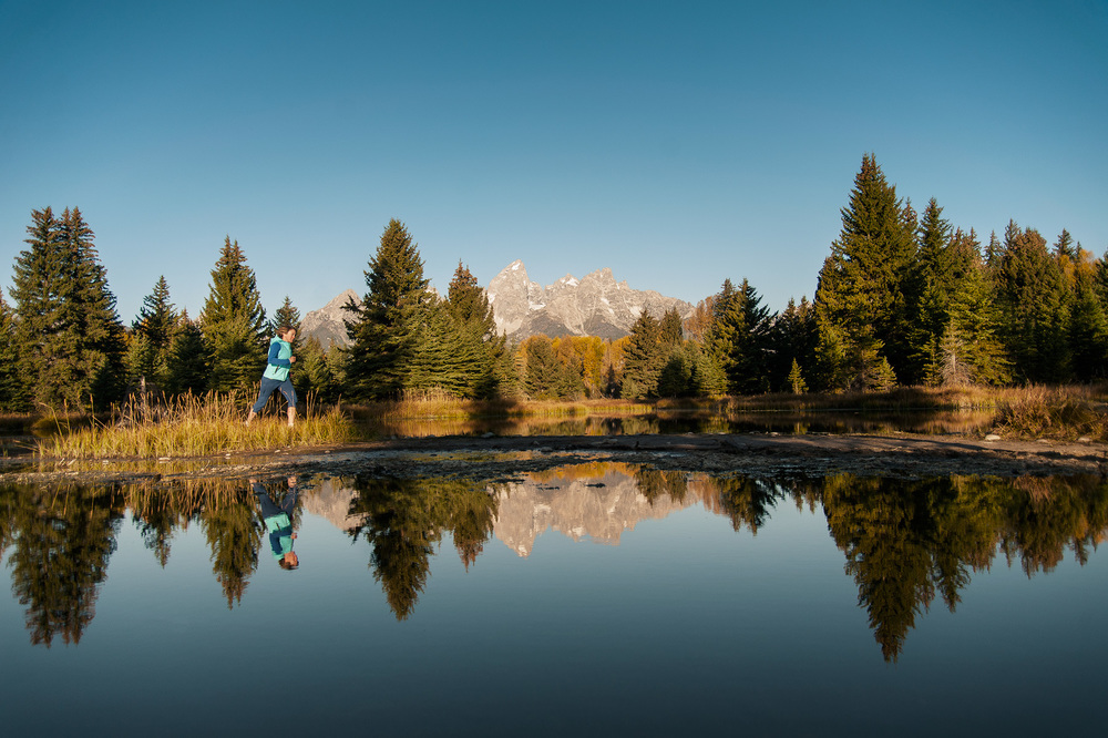 A female athlete running at sunrise in front of the Grand Teton range