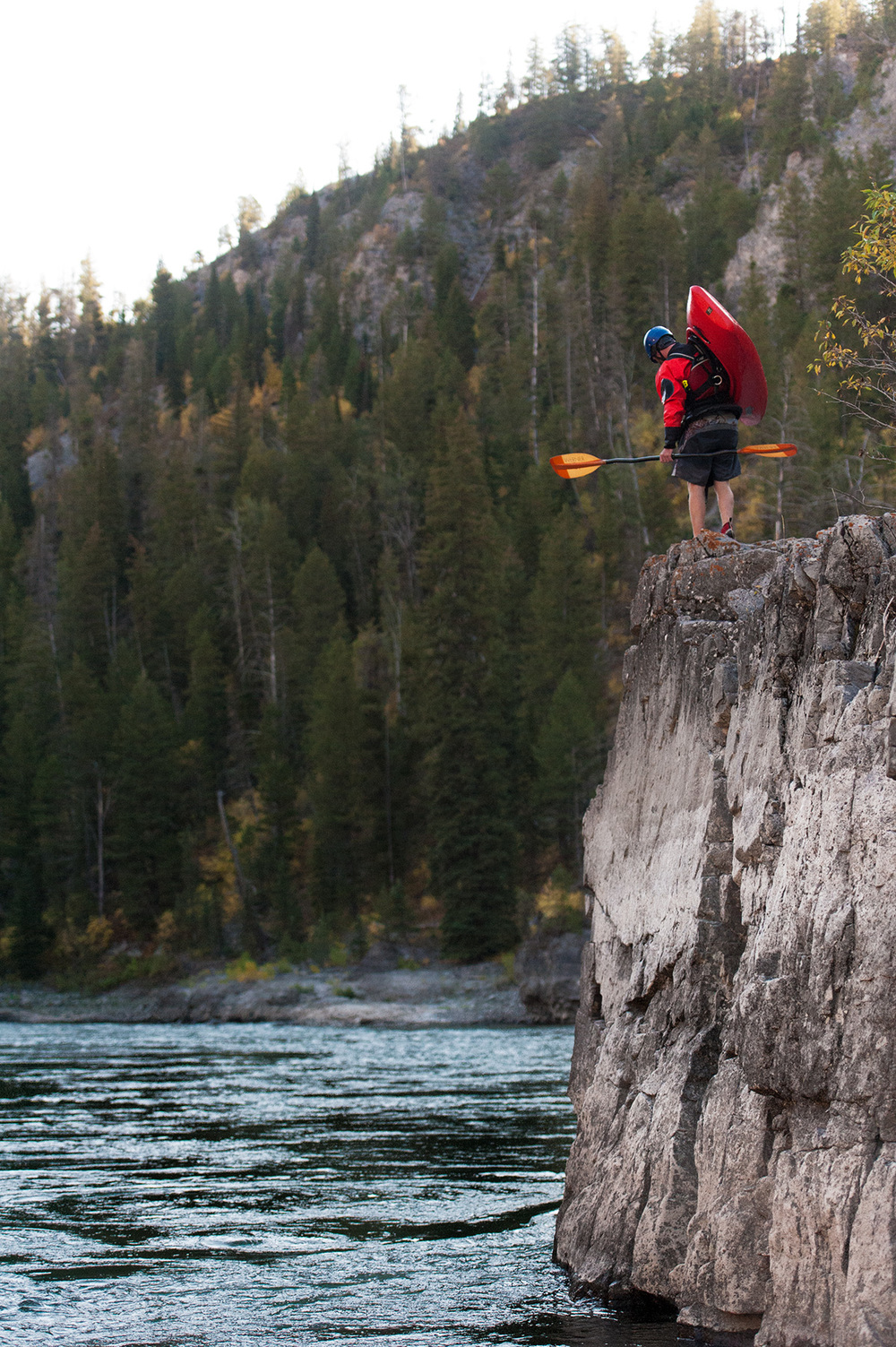 A kayaker walks upstream along the Snake River on a cliff in Wyoming