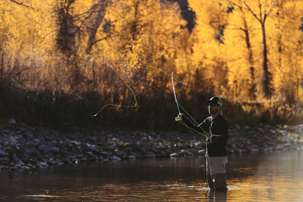 A fly fisherman casts in a fall sunrise in the Southern San Juans near Pagosa Springs, CO