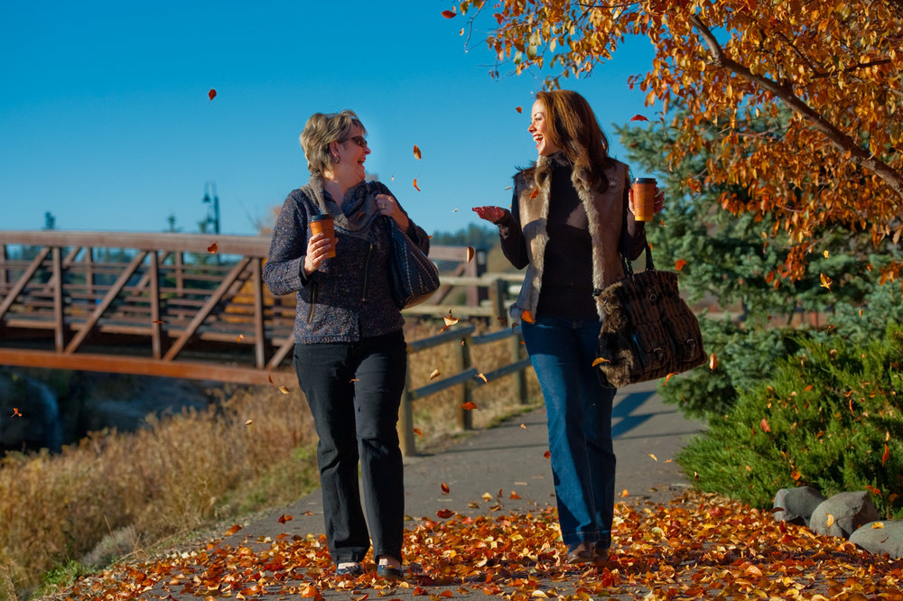 Fall fashion lifestyle image of two women walking through falling leaves while drinking coffee