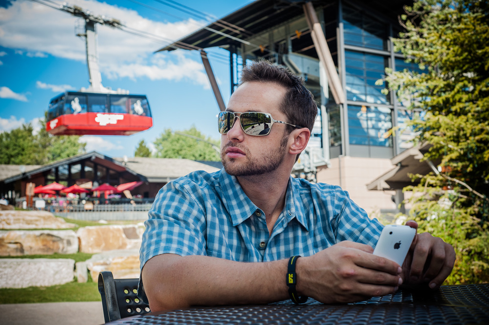 Advertising lifestlye photo featuring a Jackson Hole tram passing behind a man making plans using an iPhone