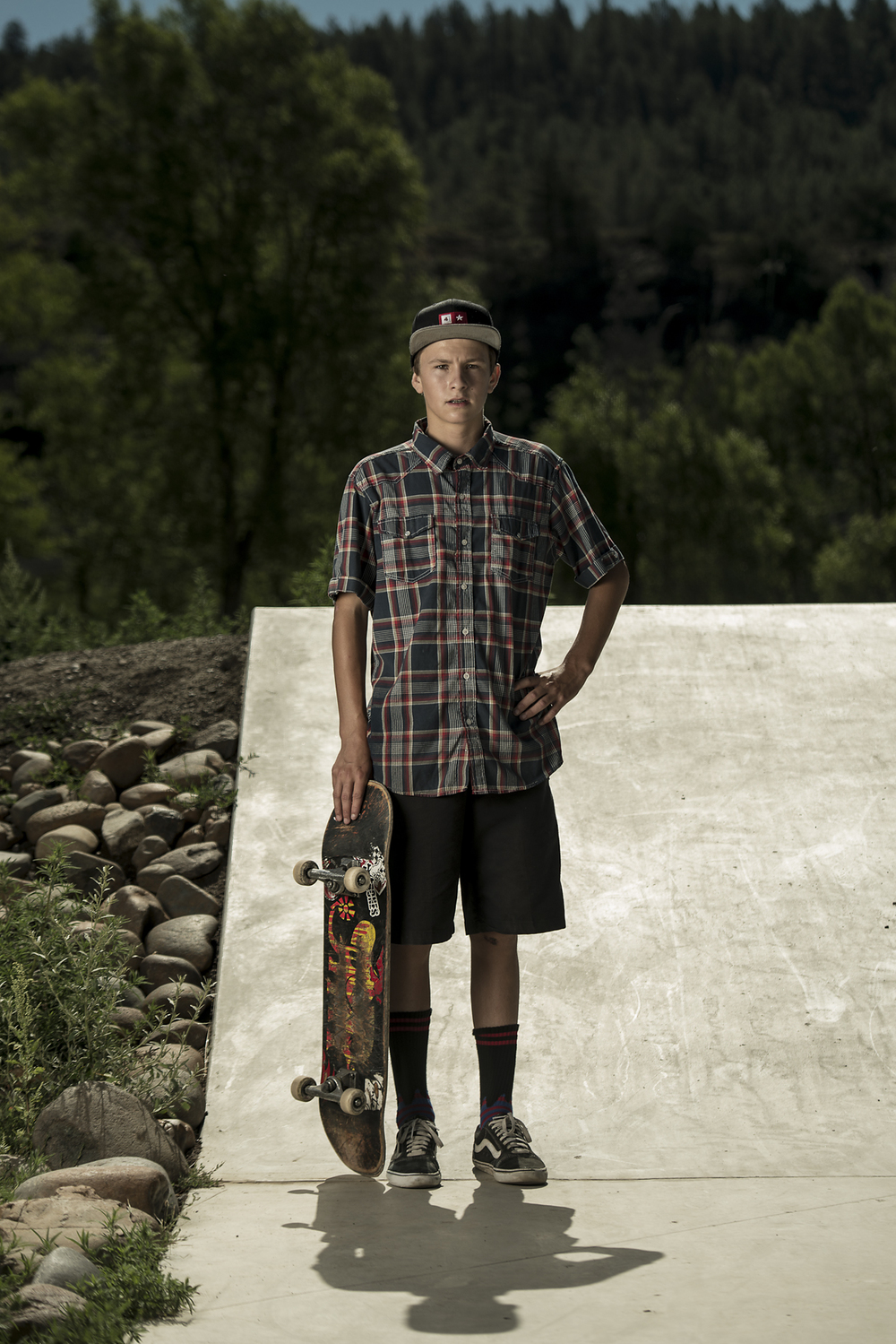 A youth skateboarder pauses for a portrait