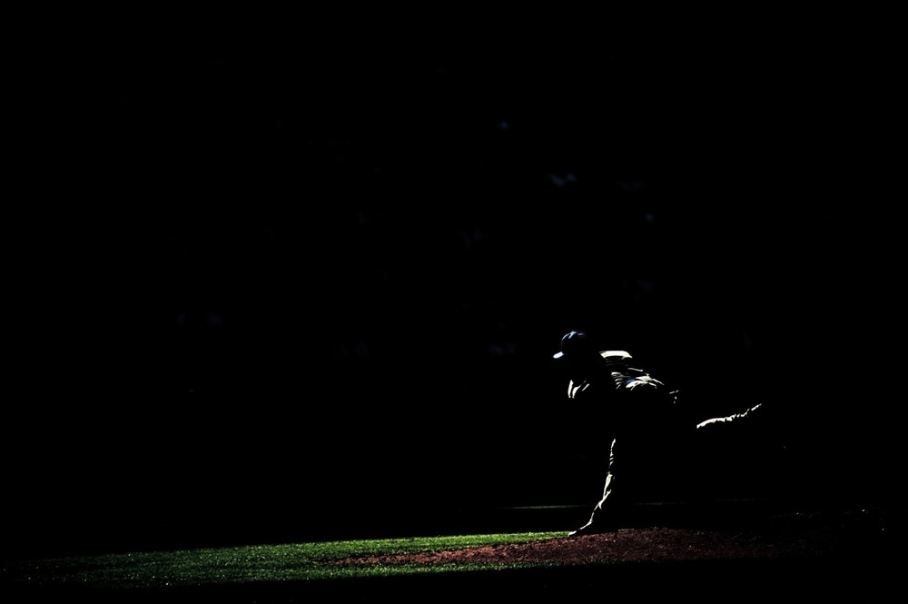 A patch of sunlight outlines a pitcher at Coors Field in Denver, CO