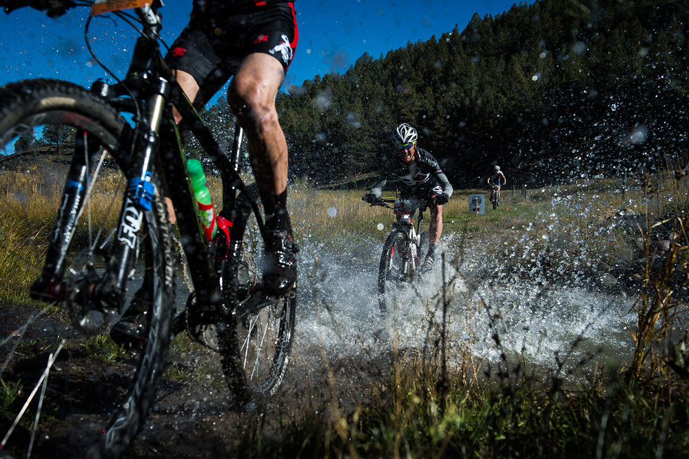 Racers splash through a creek during the GECKO Epic race near downtown Pagosa Springs, CO